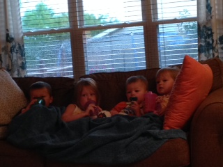 My four little loves in a rare moment of being enthralled by Curious George and looking innocent.